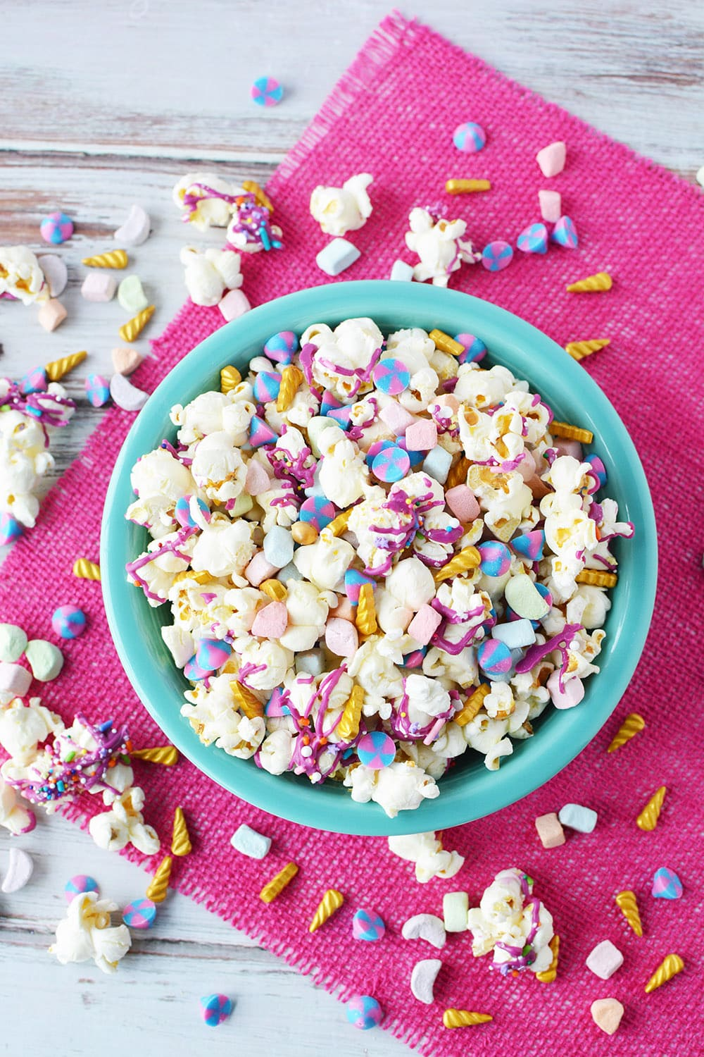 Overhead shot of unicorn popcorn in a blue bowl with a pink napkin.