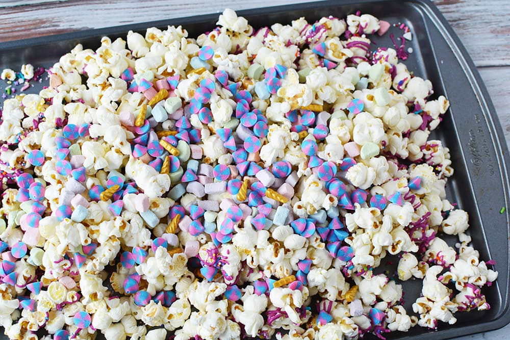 Candy and popcorn on a baking sheet.