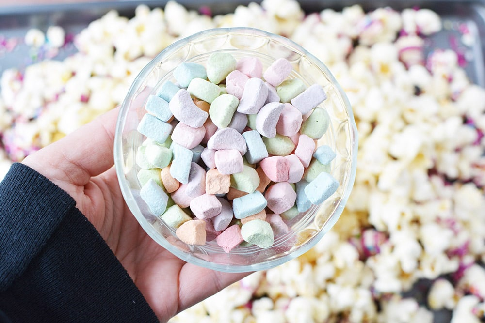 Rainbow marshmallows in a bowl over popcorn.