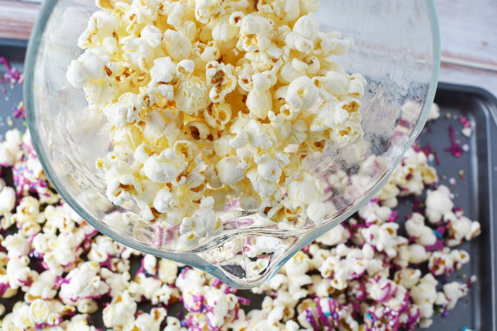 Bowl of popcorn over a baking sheet with more popcorn.