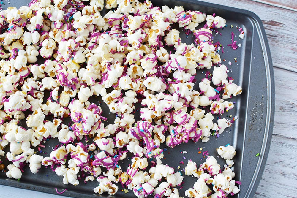 Baking sheet of popcorn with candy drizzle on it.