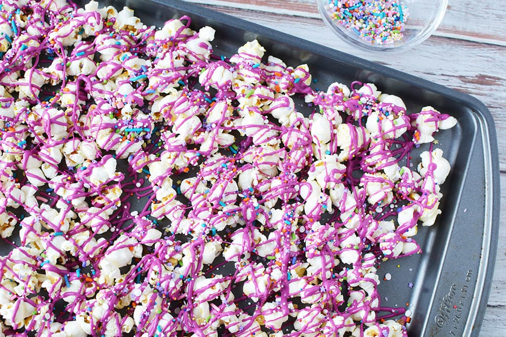 Pink candy melts drizzled over popcorn.