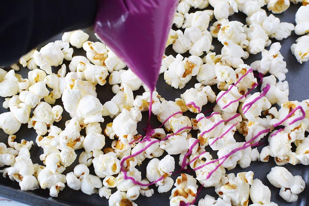 Drizzling pink chocolate onto plain popcorn.