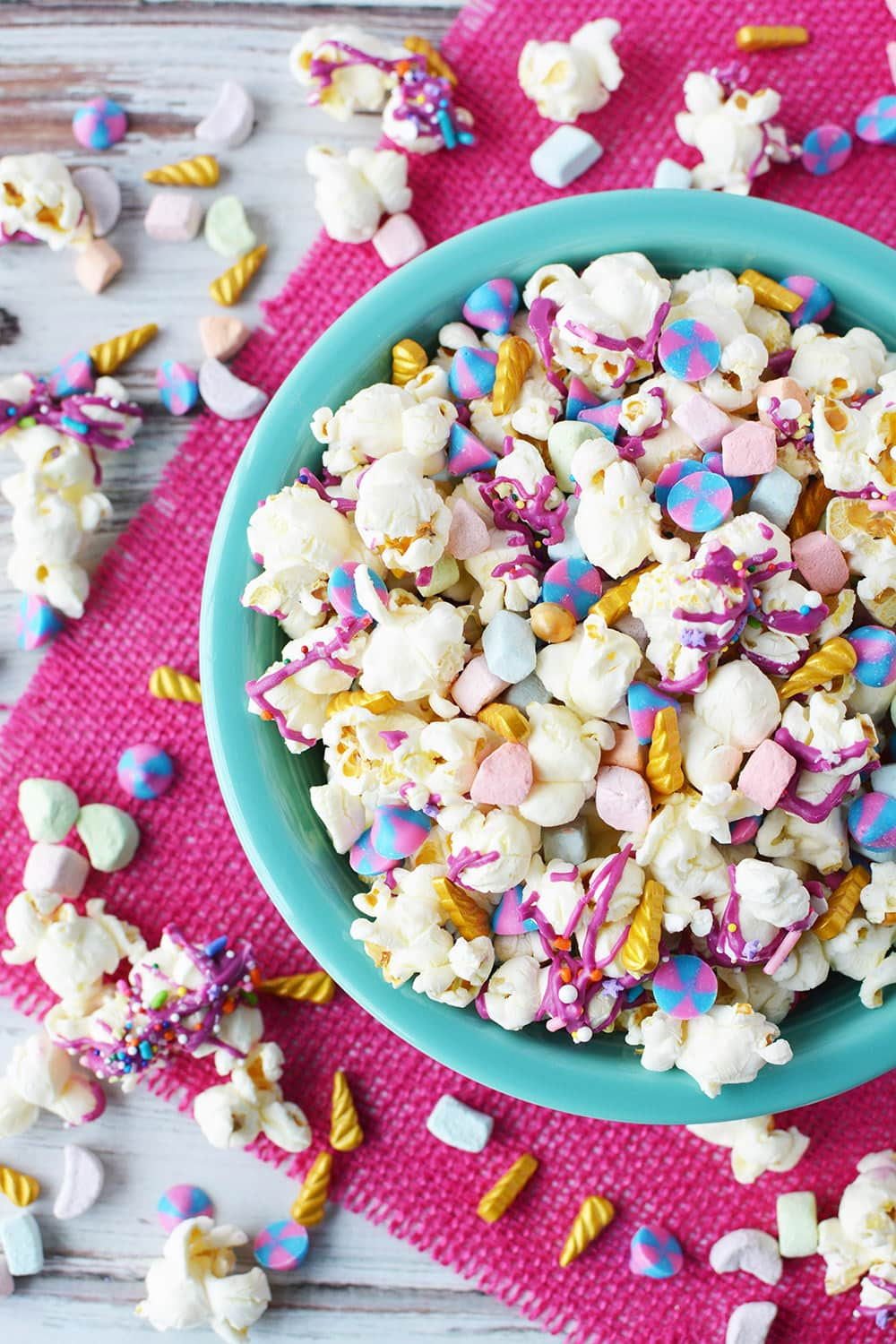 Unicorn popcorn in a bowl with more spilling out on the table.