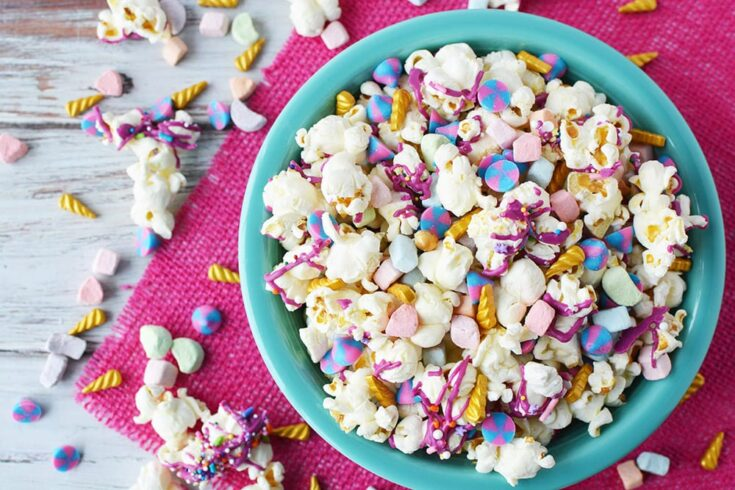 Blue bowl full of unicorn popcorn with popcorn and candies on table with a pink napkin.