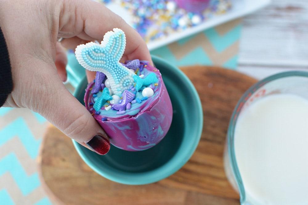 Dropping a mermaid hot chocolate bomb into a mug.