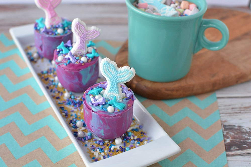 Mermaid hot chocolate melts on a plate next to a mug of hot chocolate.