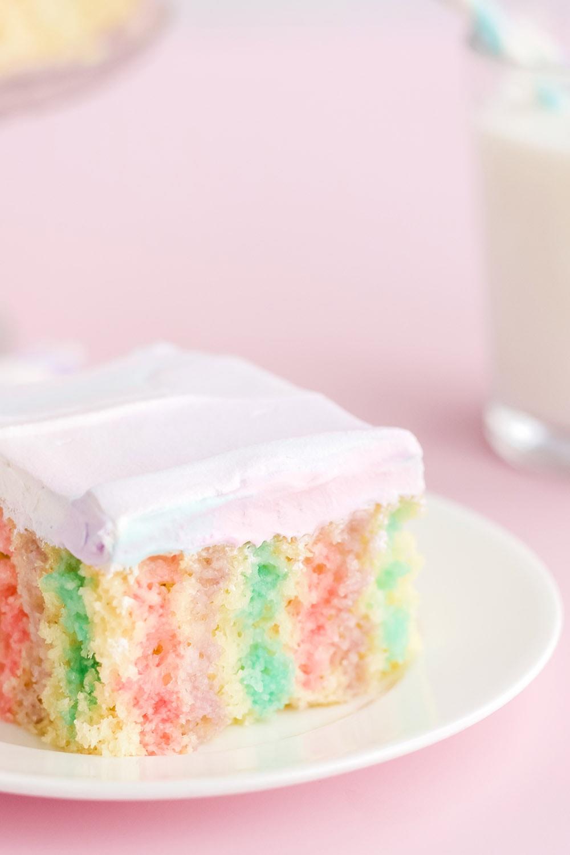 Unicorn poke cake on a white plate.