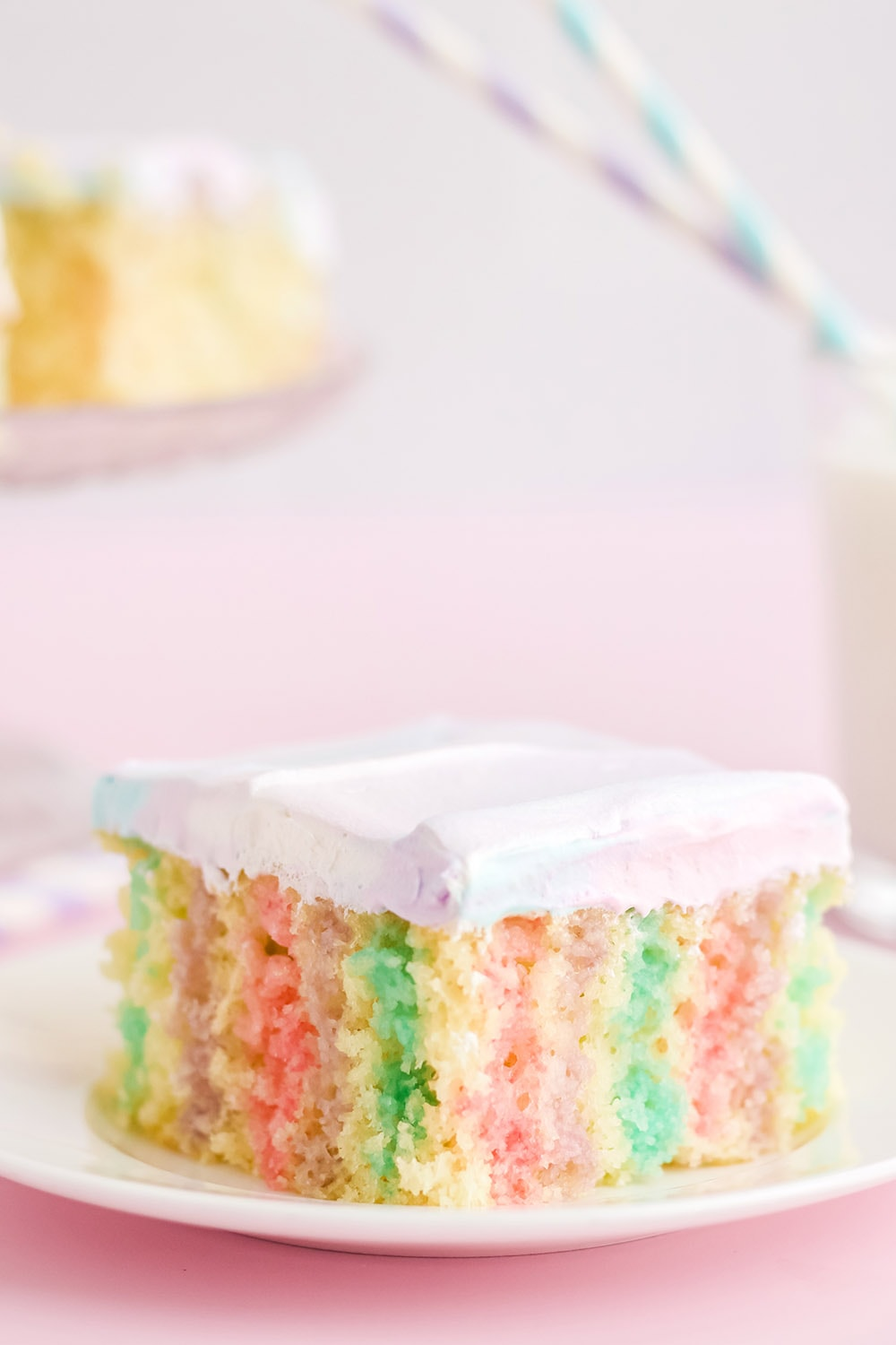 Unicorn poke cake on a plate with a pink background.