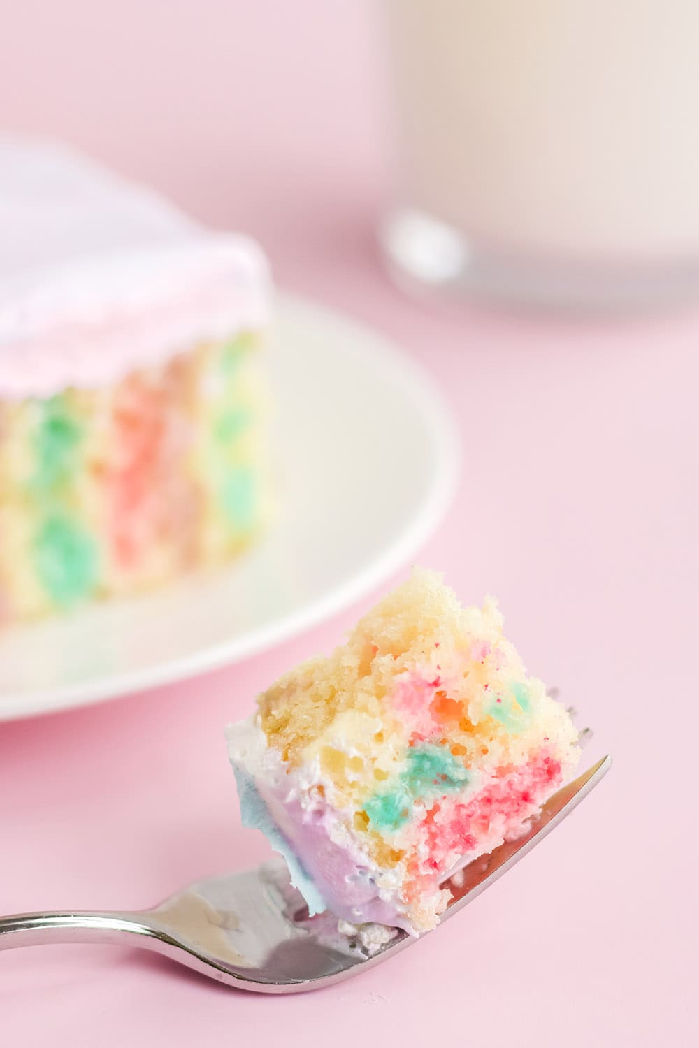 Fork with cake on it with a slice of poke cake on a plate.