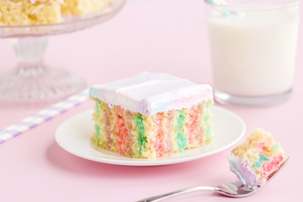 Rainbow poke cake on a white plate on a pink table with milk.