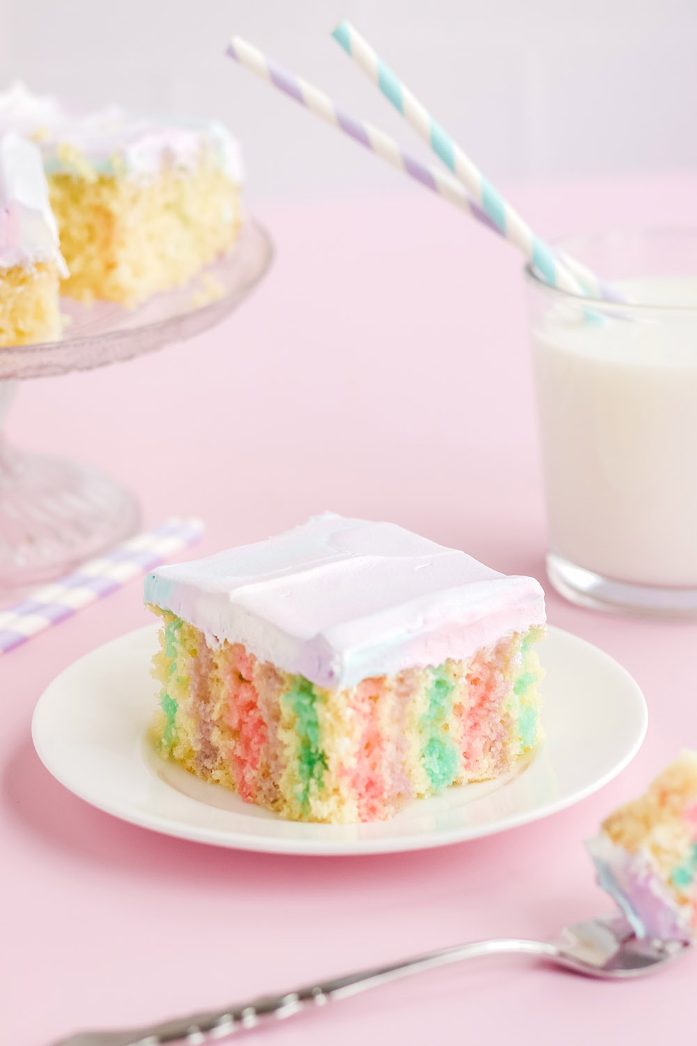 Colorful cake on a plate with milk and more cake in the background.