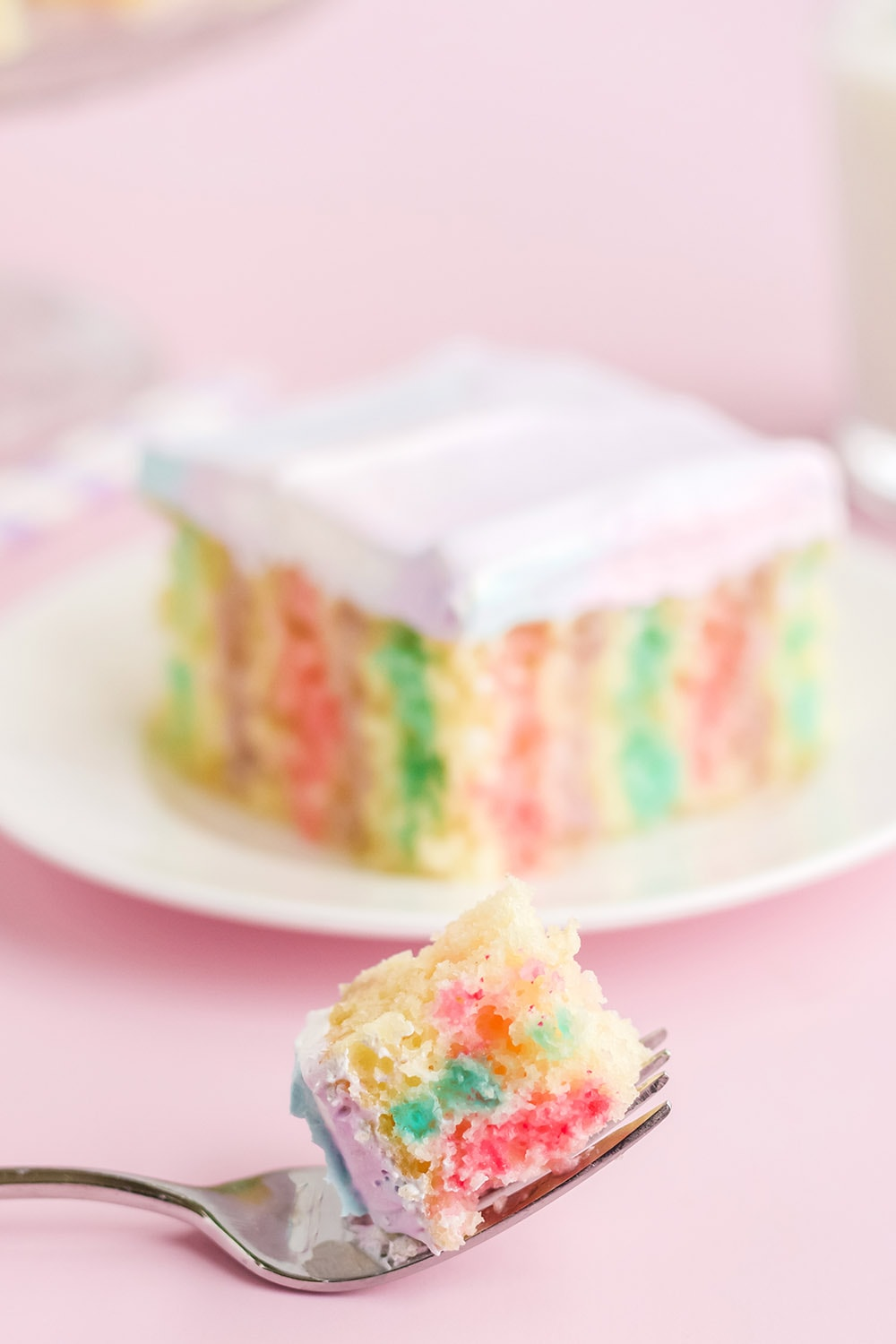 Colorful jello poke cake on a plate with a forkful in front.