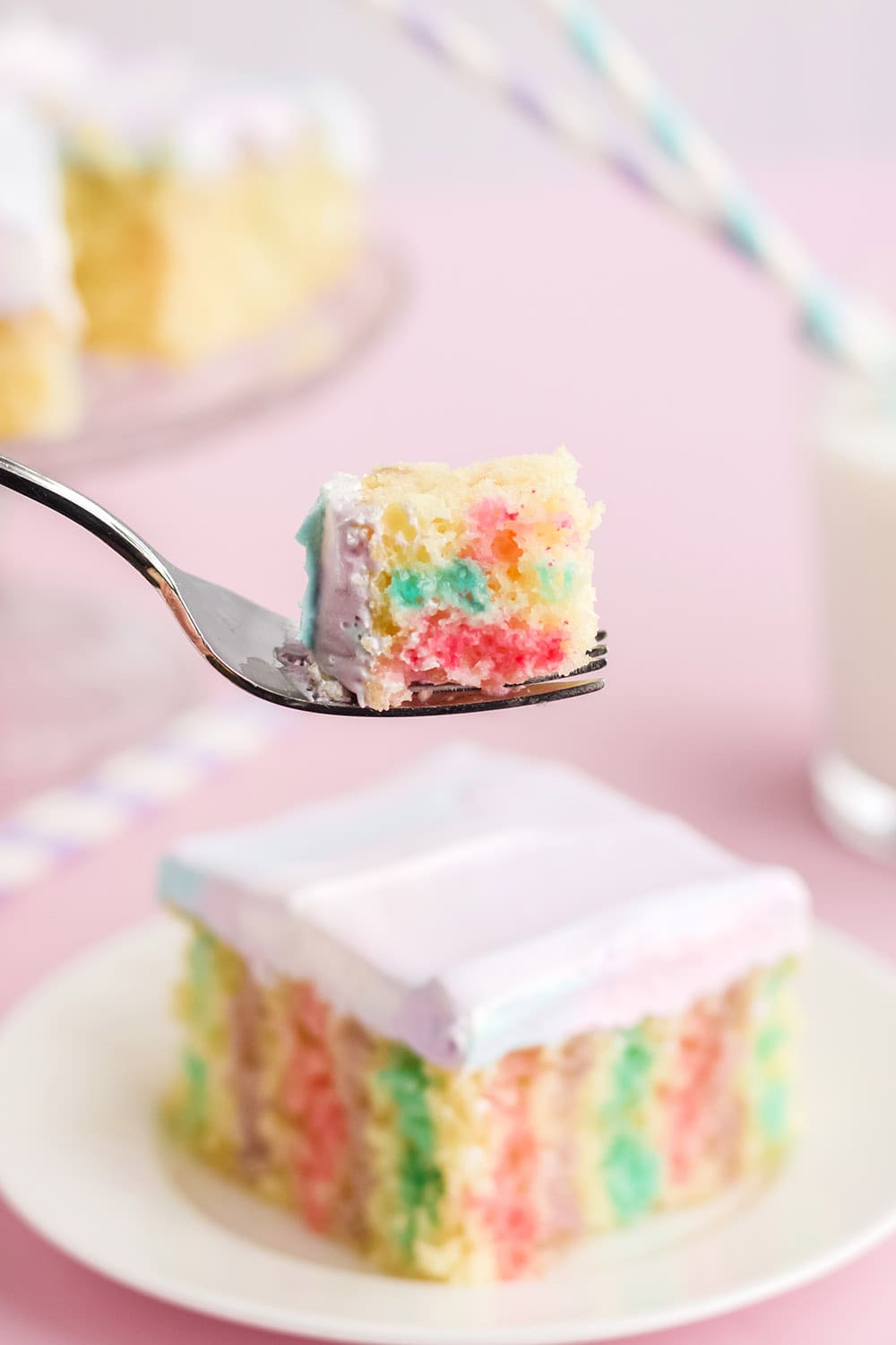 Fork with cake on it in front of a poke cake on a plate.