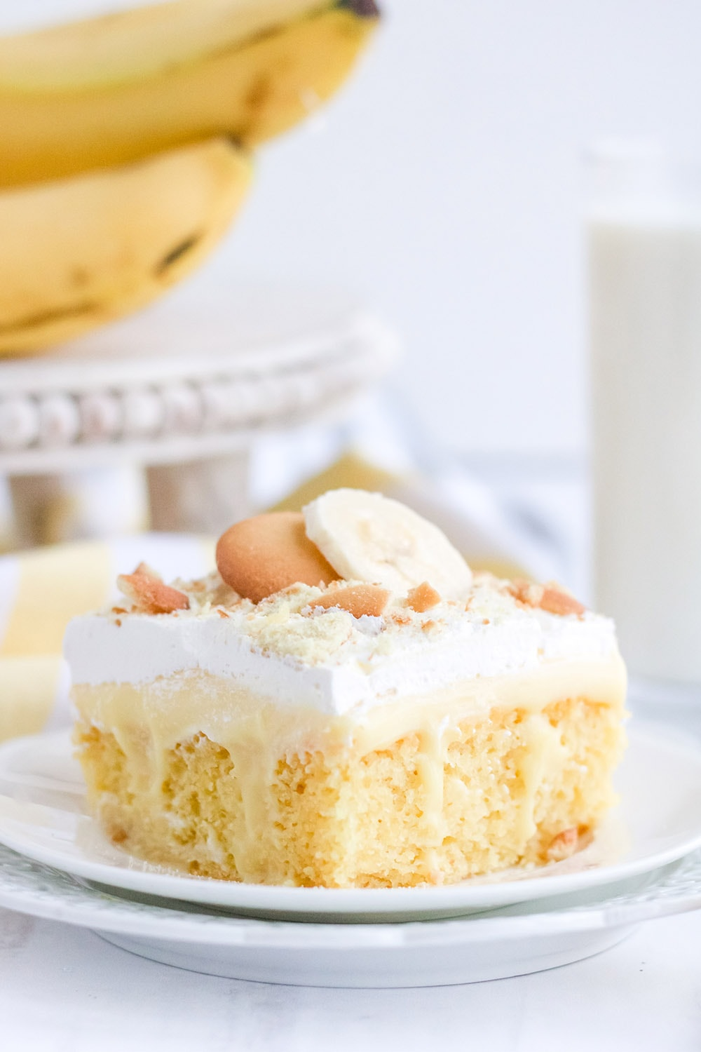 Yellow cake on a white plate with bananas and cookies.