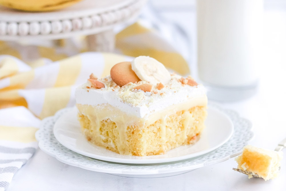 Yellow cake on a white plate on a white table with bananas and cookies.