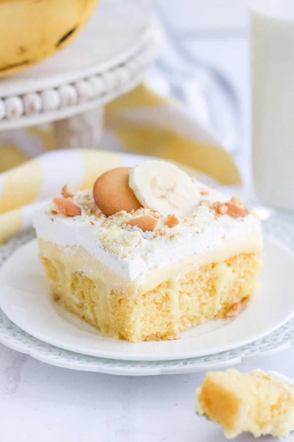 Banana pudding cake topped with whipped cream and cookies.