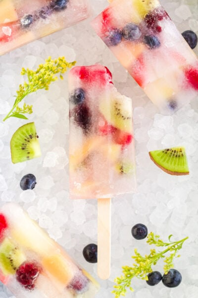 Rainbow fruit pops on ice with fresh fruit pieces.