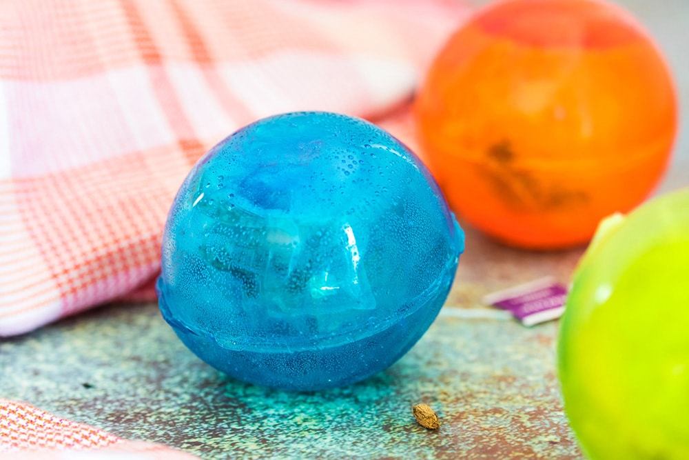 Hot tea bomb in blue and orange sitting on a counter.