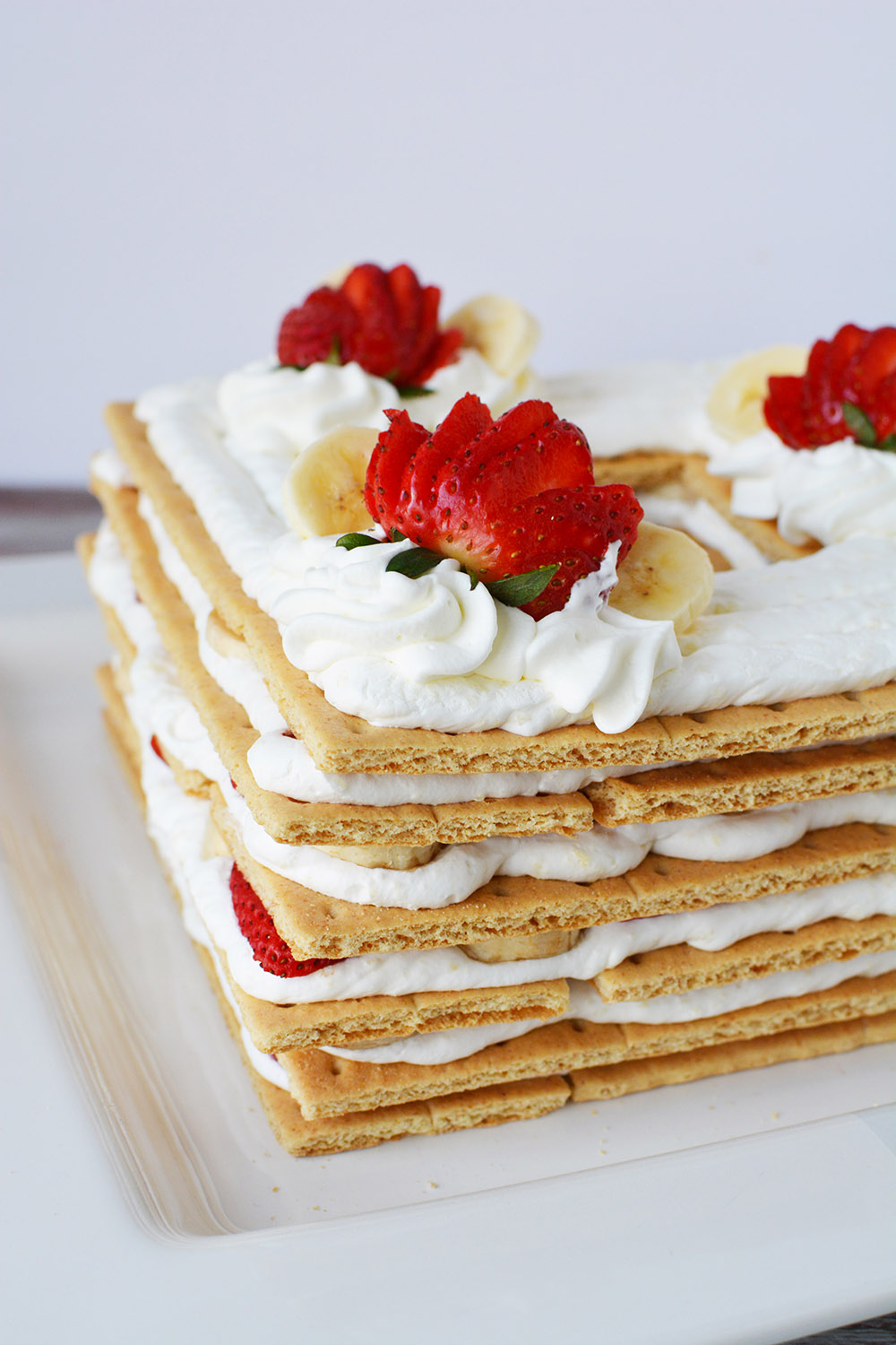 Layers of dessert into an ice box cake with strawberries.