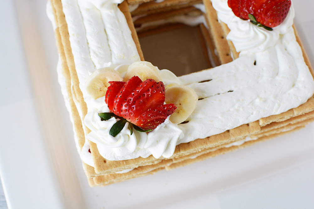Strawberries and whipped cream on top of graham crackers.