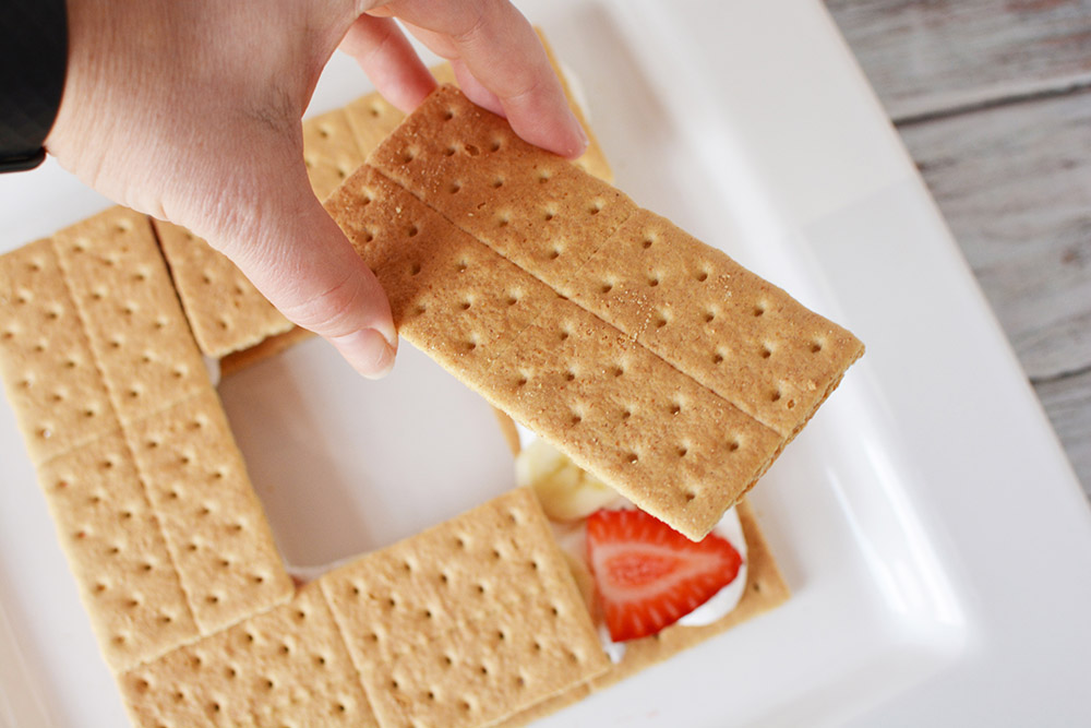 Stacking graham crackers on top of a strawberry.