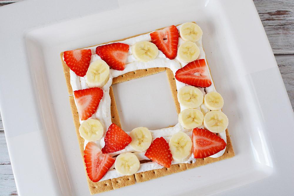 Strawberries, bananas, and whipped cream on graham crackers.