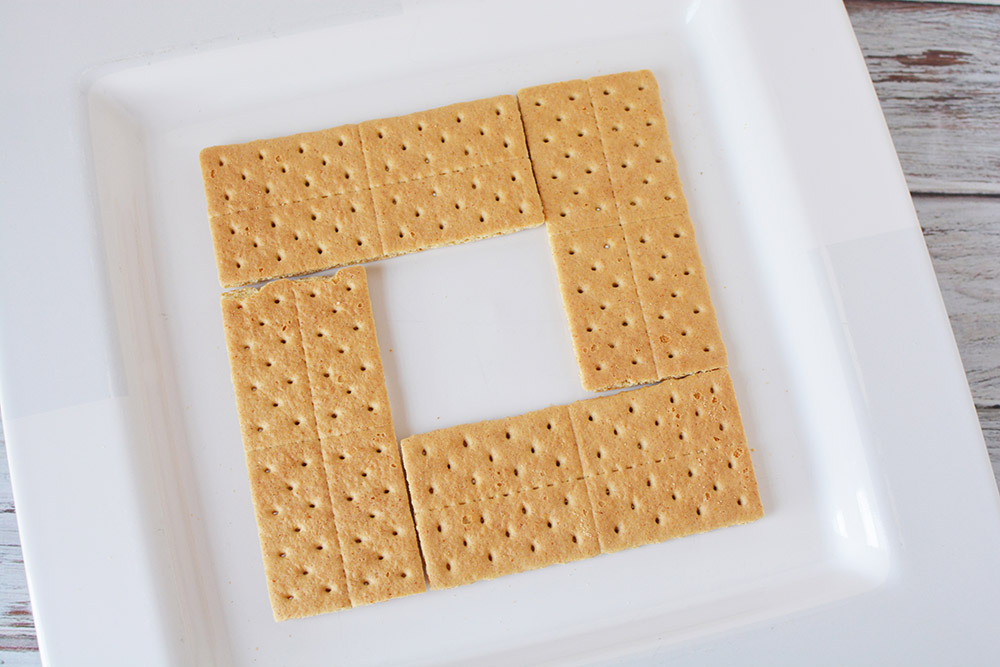 Lining up graham crackers onto a square plate.