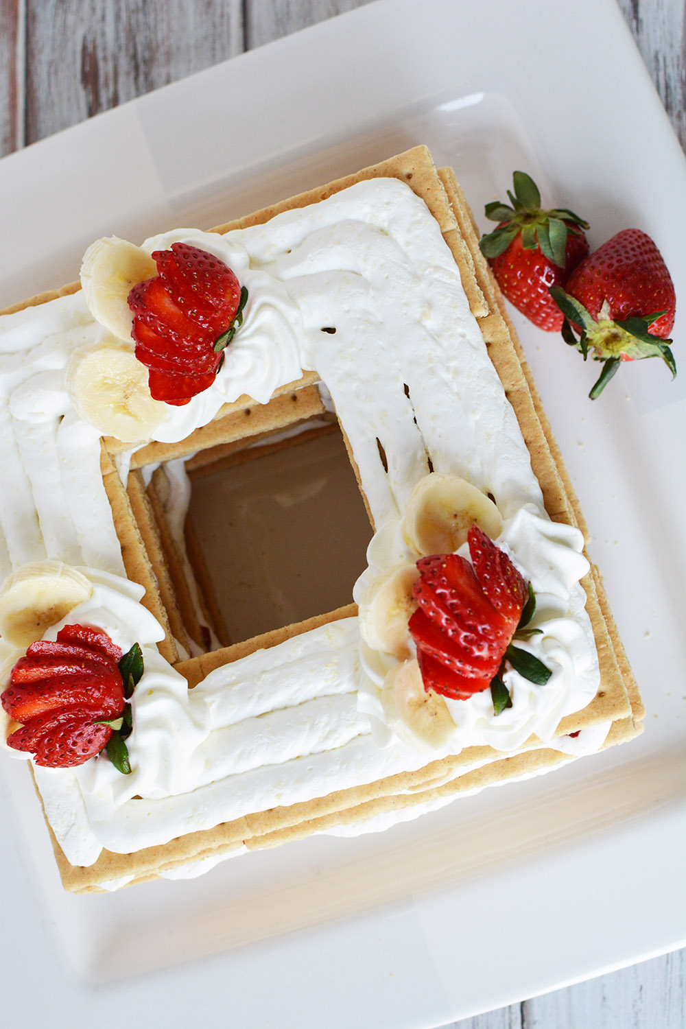 Overhead shot of ice box cake topped with whipped cream and strawberries.