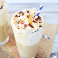 Caramel drink with whipped topping and sugar crunch with blue straw.