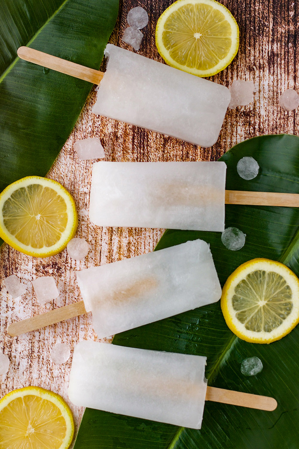 Four ice pops on a table with ice cubes, leaves, and lemon slices.