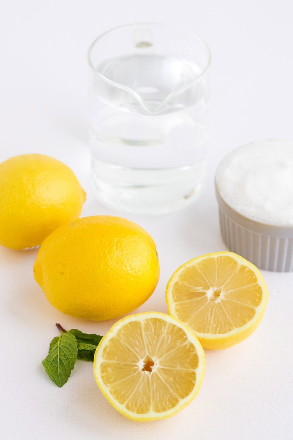 Water, lemons, and sugar on a table.