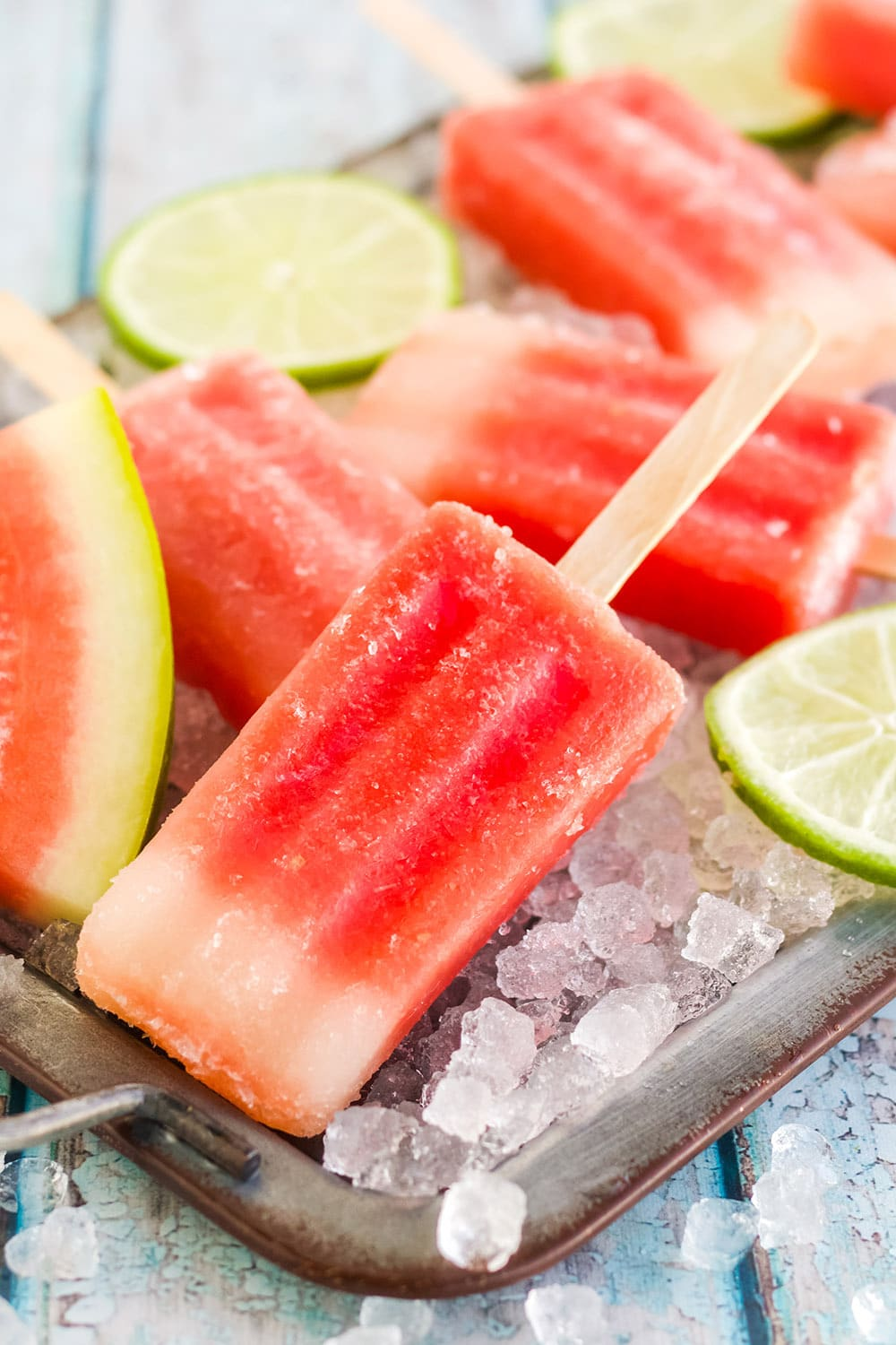 Red popsicles on a tray with watermelon.