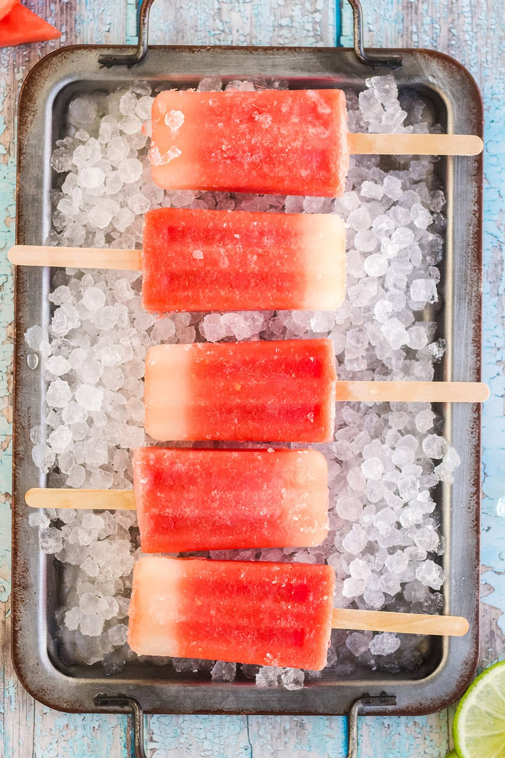 Watermelon pops lined up in a tray with ice.