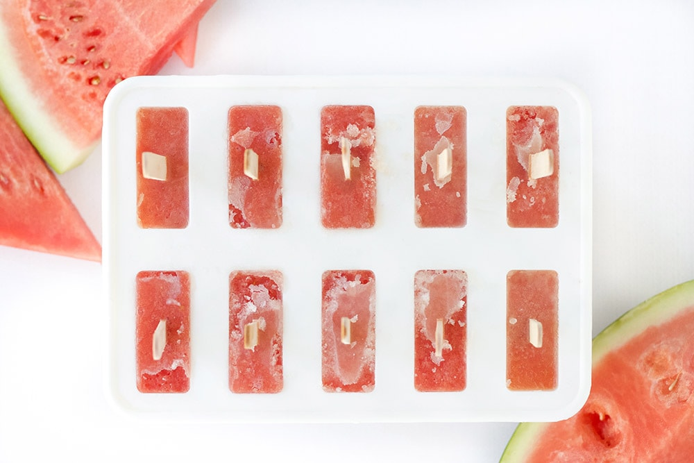 Popsicle mold with red liquid and popsicles sticks in it.