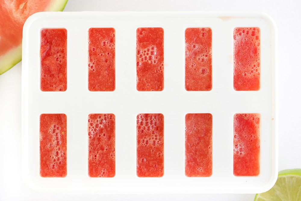Red popsicles poured into a mold.