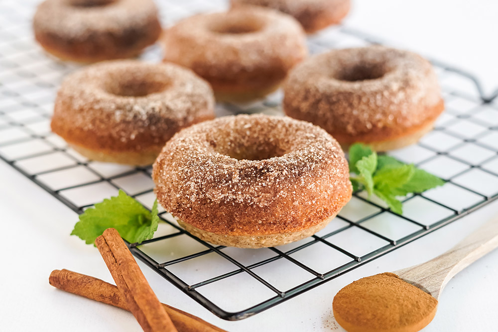 Apple cider donuts with cinnamon on a rack.