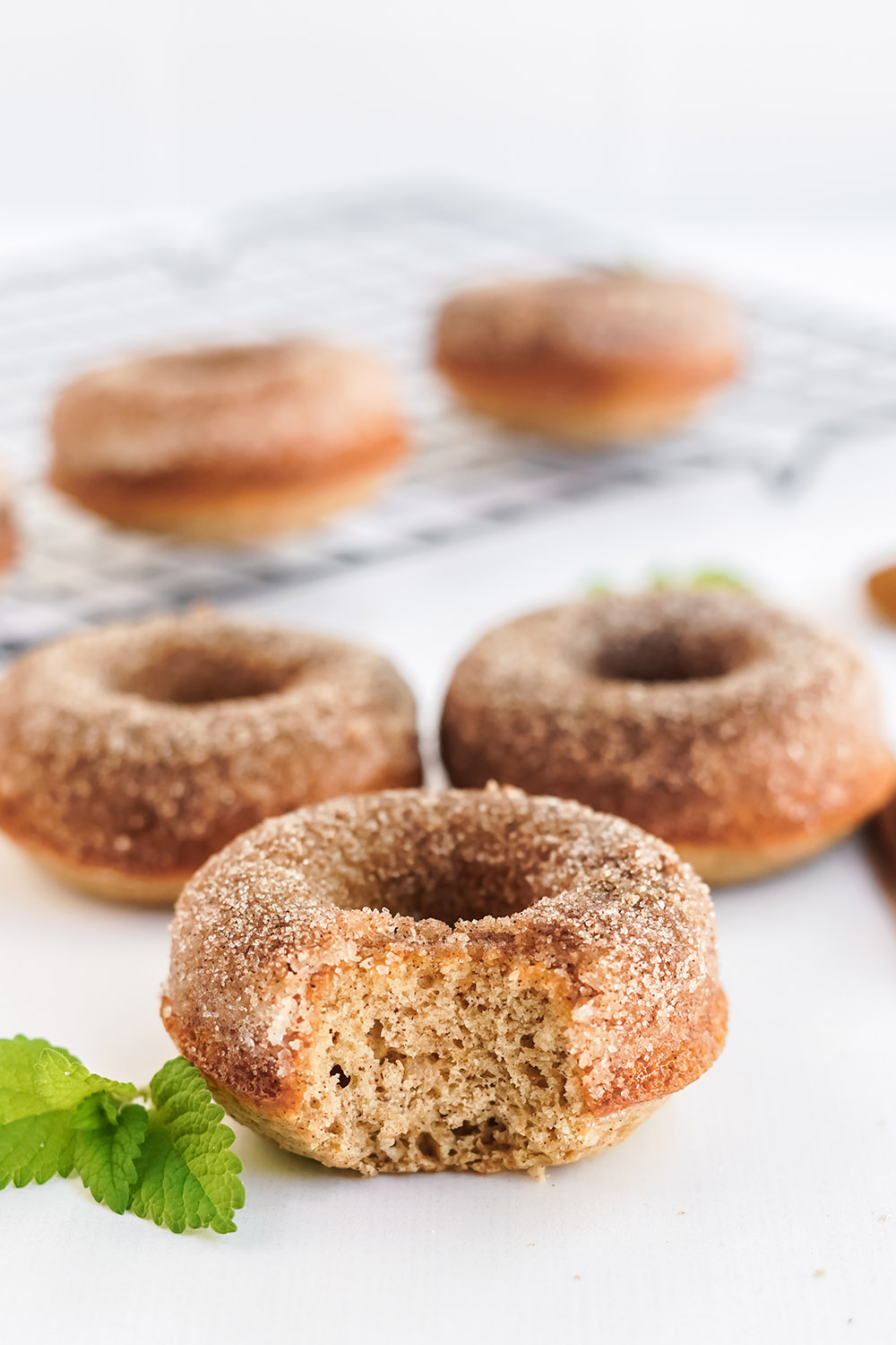 Three apple cider donuts on a table with more on a rack in the background. One donut has a bite taken out of it.