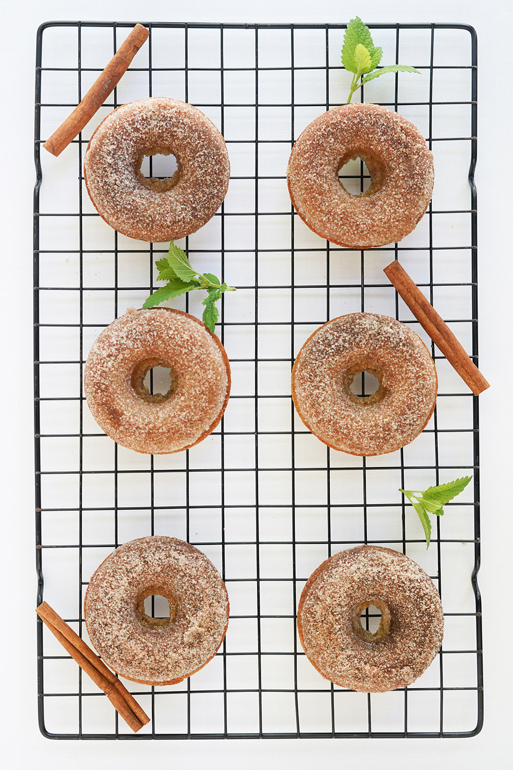 Donuts, cinnamon sticks, and green leaves on a wire rack.