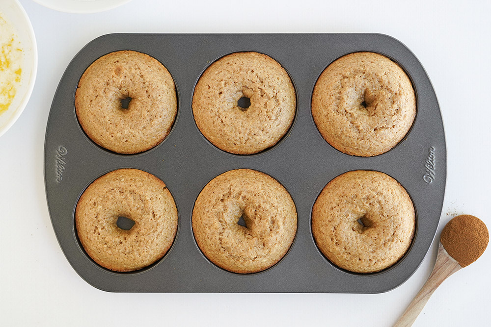 Donuts in a pan after being baked.