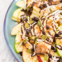 Green and red apple slices on a plate topped with, chocolate, caramel, nuts, and toppings.