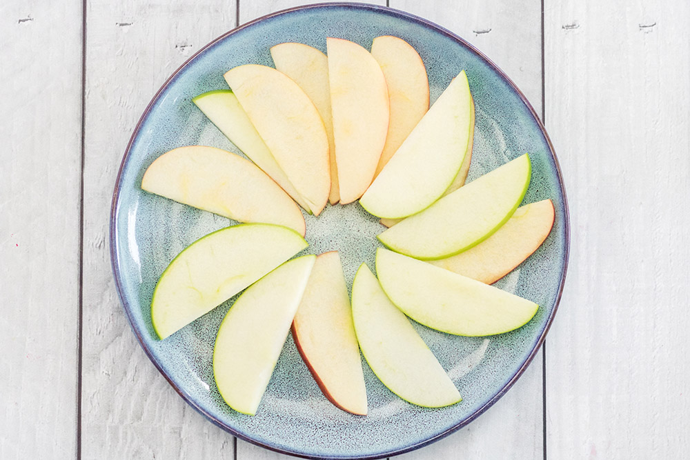 Apple slices arranged on a blue plate.