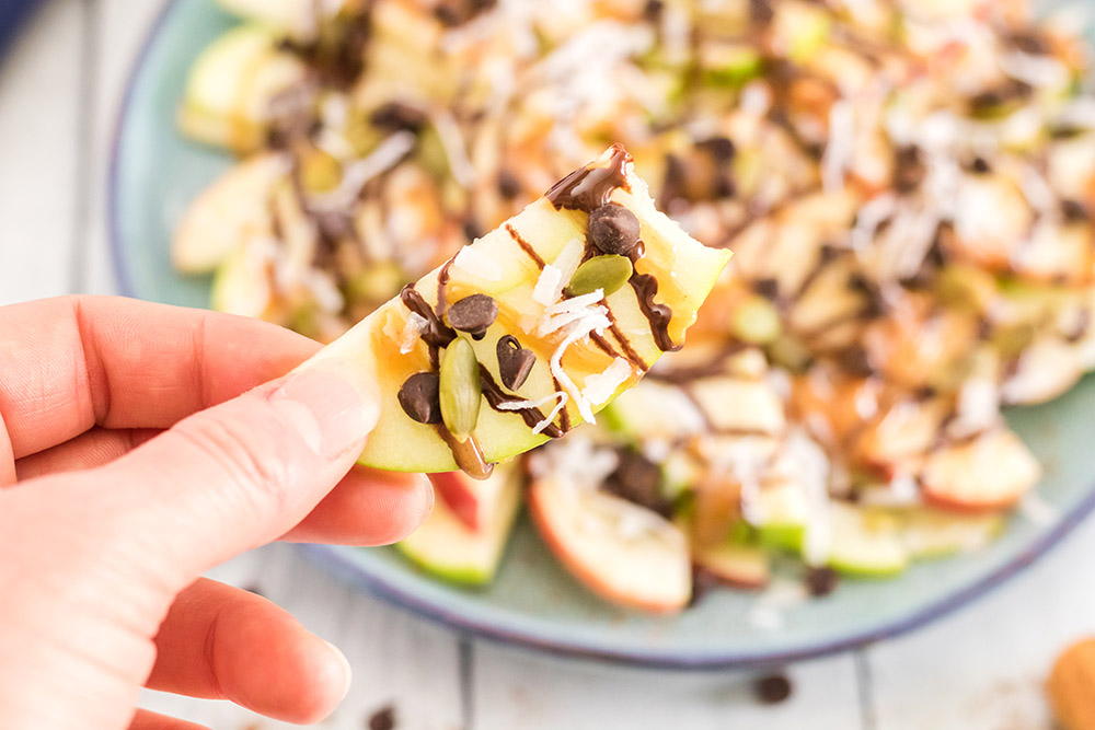 Holding an apple nacho above a plate of apple slices with toppings.