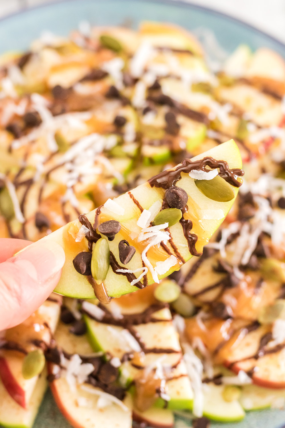 Apples topped with nuts, caramel, and chocolate for apple nachos.