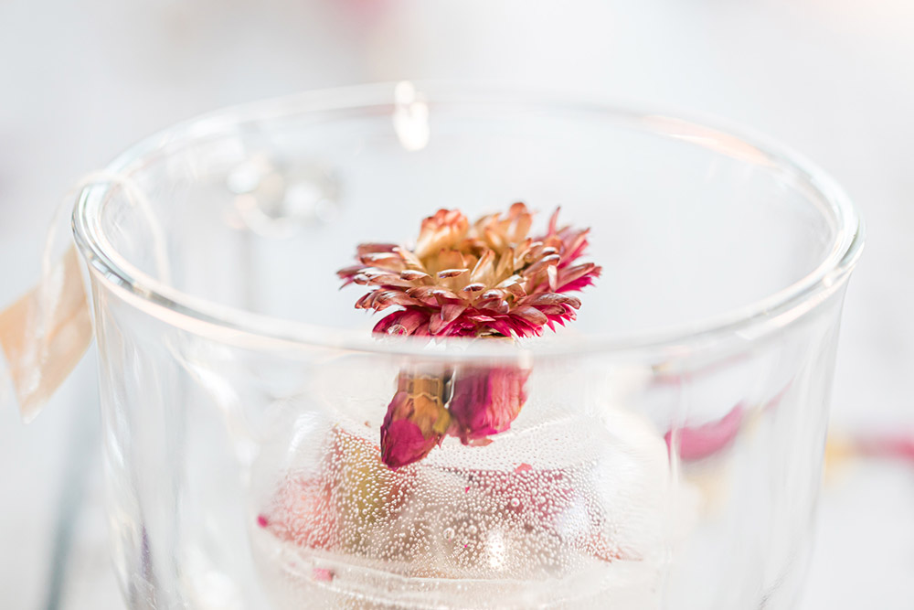 Half of a clear tea orb with a flower in it.