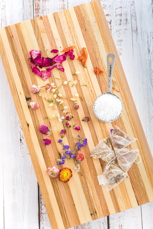 Board full of ingredients to make floral tea globes.