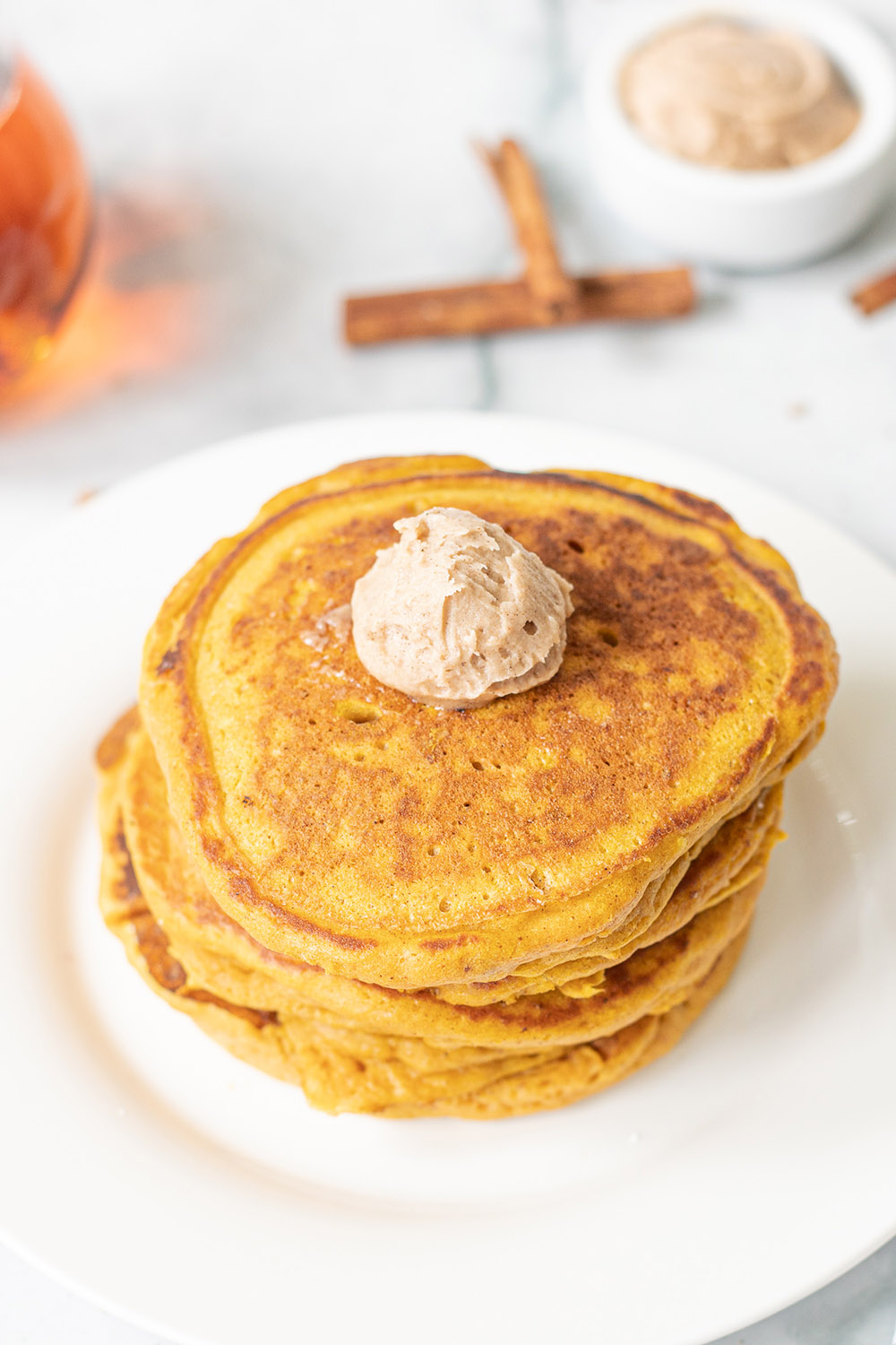 Pancakes stacked on a plate with butter and cinnamon sticks on the table.