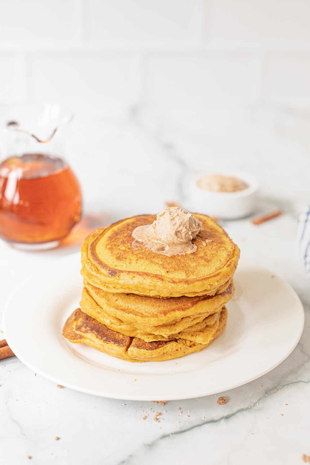Pancakes on a plate topped with honey butter and a pitcher of syrup in the background.