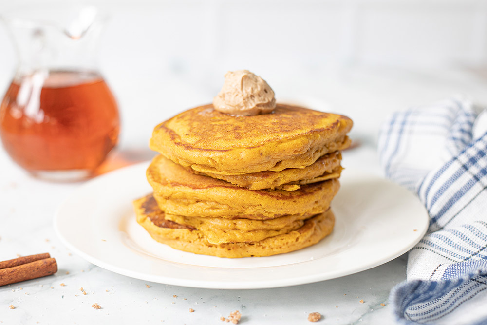 Pancakes stacked on a plate with syrup in the background.