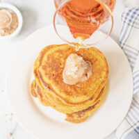 Pouring syrup over pumpkin pancakes with a scoop of cinnamon butter.
